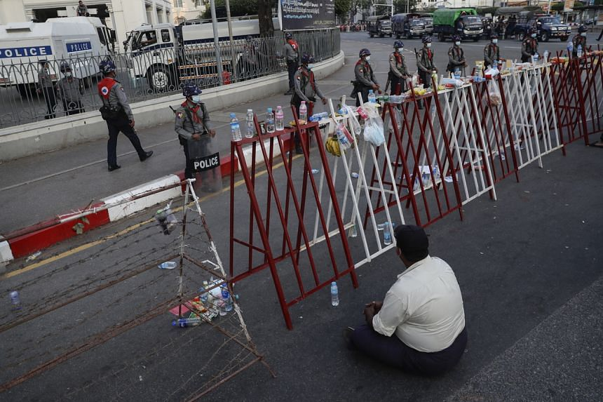A demonstrator sitting in front of a barricade during a protest near the Yangon city hall, on Feb 7, 2021.