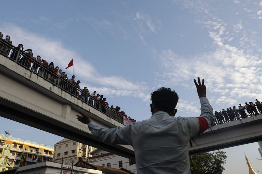 A man gesturing with the three-finger salute as other demonstrators gather on a footbridge in Yangon, Myanmar, on Feb 7, 2021.