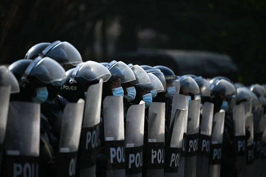 Riot police block the street as protesters hold a demonstration against the military coup in Yangon on Feb 7, 2021.