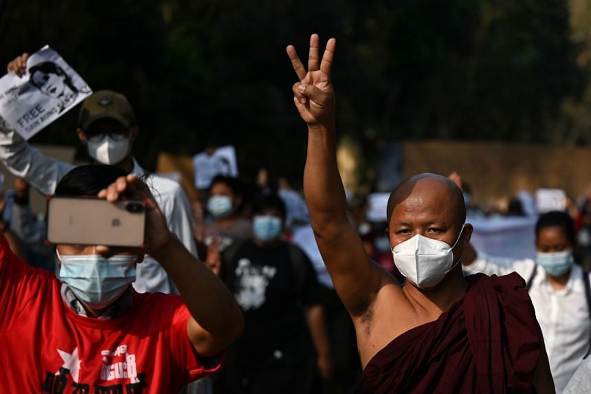 A monk holds up the three finger salute during a demonstration against the military coup in Yangon on Feb 7, 2021.