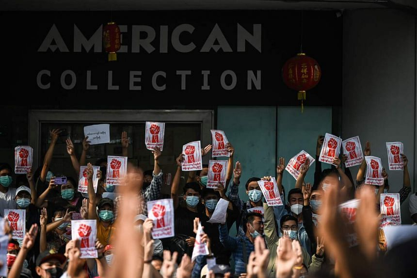 Protesters hold up the three finger salute and placards during a demonstration against the military coup in Yangon on Feb 7, 2021.