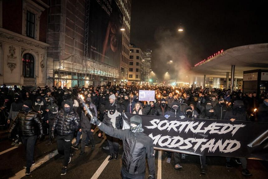 """Protesters hold a poster reading """"Black-clad Resistance"""" in Copenhagen, Denmark, on Jan 23, 2021."""
