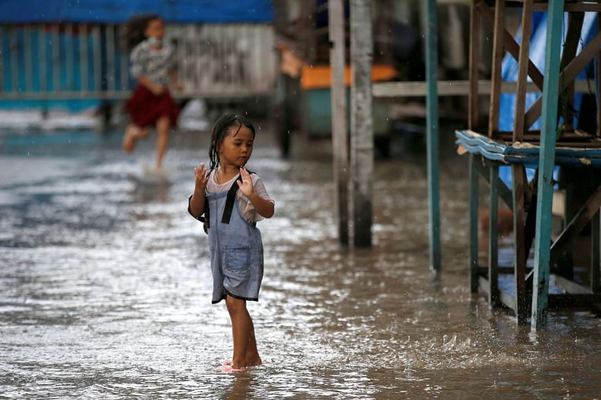 A girl plays on a street affected by floods in Jakarta, on Feb 8, 2021.