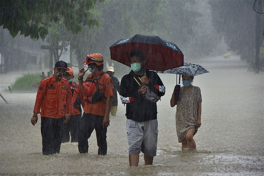 Residents make their way along a flooded street in Bekasi, on the outskirts of Jakarta, on Feb 8, 2021.