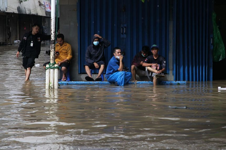 Residents sit outside their flooded home in Jakarta on Feb 8, 2021, as heavy rain inundated areas beside the city's rivers.