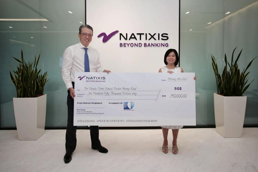 Mr Pin Chua (left) presents a cheque to general manager of The Straits Times School Pocket Money Fund, Ms Tan Bee Heong, at Natixis Singapore Branch office, on Feb 8, 2021.