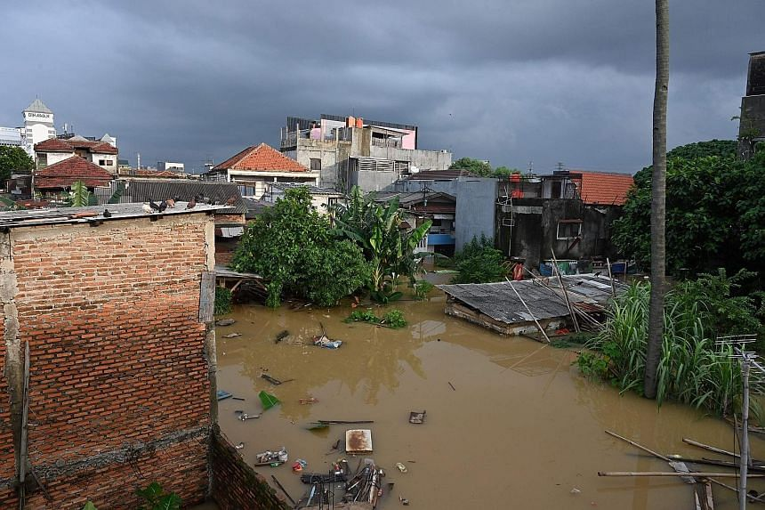 Flood waters submerging homes in south Jakarta after heavy rain yesterday. More than 1,000 people in the Indonesian capital have been evacuated. The wet conditions are expected to continue until next month or April. PHOTO: AGENCE FRANCE-PRESSE