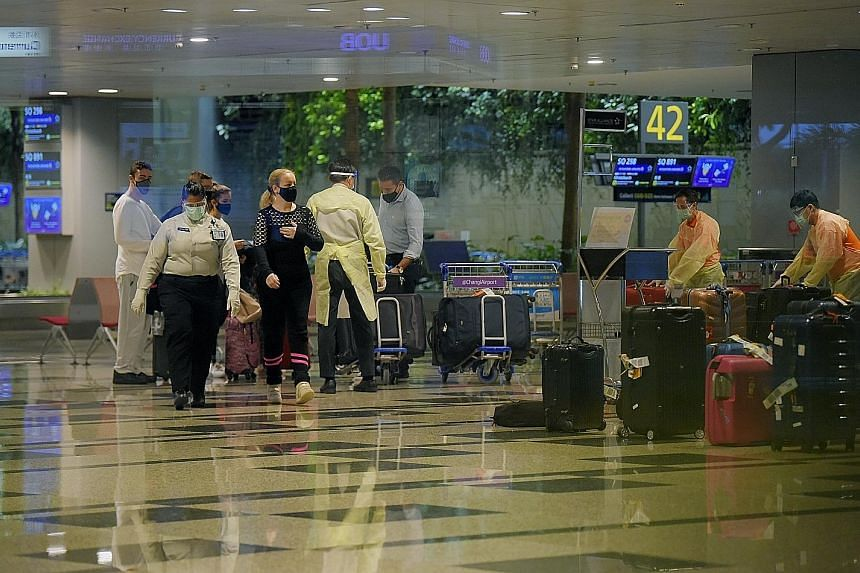 Passengers arriving at Changi Airport yesterday. The Immigration and Checkpoints Authority said traveller volume fell as demand for air travel came to a halt, with many countries imposing strict border control measures due to the Covid-19 pandemic. J