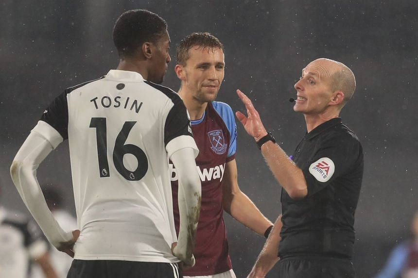 West Ham's Tomas Soucek (centre) argues with referee Mike Dean (right) as Fulham's Tosin Adarabioyo (L) looks on.