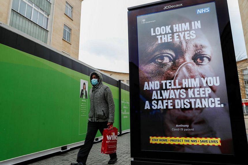 A person walks past a public health information poster in Bristol, Britain.