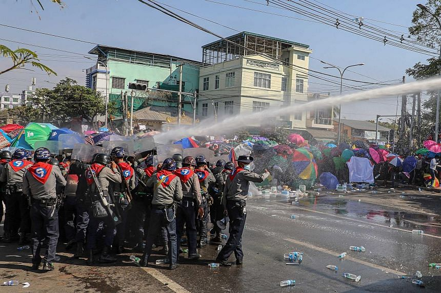Police using water cannon against demonstrators in Mandalay yesterday as they protested against the military coup and demanded the release of elected leader Aung San Suu Kyi. Police blocking a road during a protest in Naypyitaw yesterday. Ugly confro