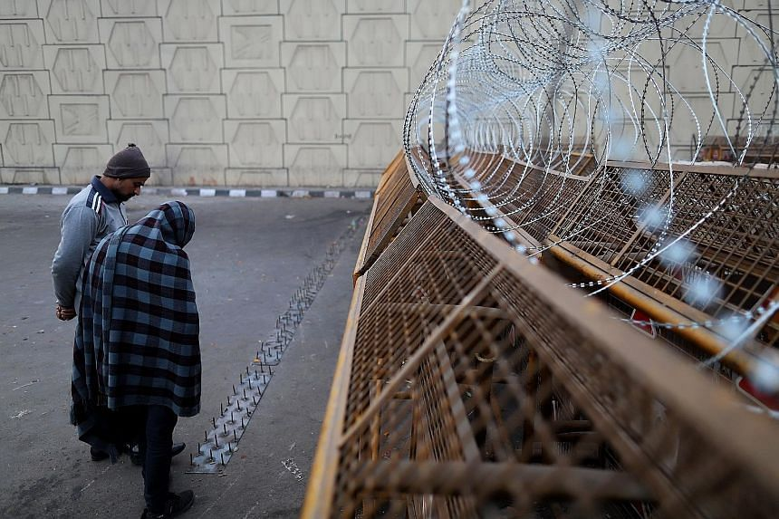 Farmers inspecting a barricade erected by the police, which blocks a highway in Ghazipur on the outskirts of New Delhi, India, last week. The government fortified Delhi's borders and asked Twitter to block the accounts of key protest leaders as it br
