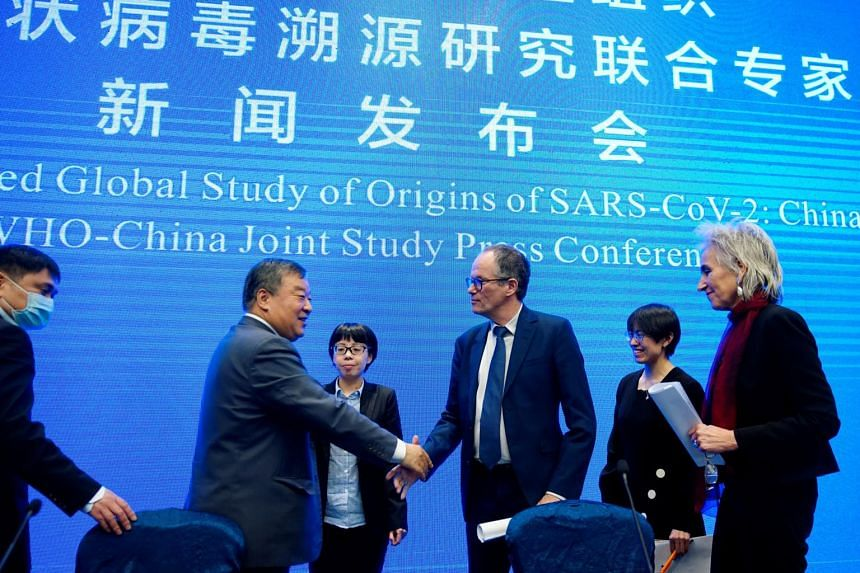Peter Ben Embarek, a member of the World Health Organisation team, shakes hands with Liang Wannian, head of expert panel on Covid-19 response, at the end a news conference in Wuhan, on Feb 9, 2021.