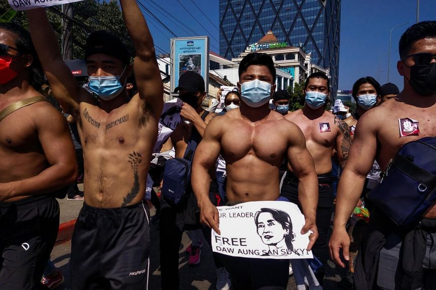 Shirtless men holding signs calling for the release of detained Myanmar civilian leader Aung San Suu Kyi march in Yangon, on Feb 10, 2021.