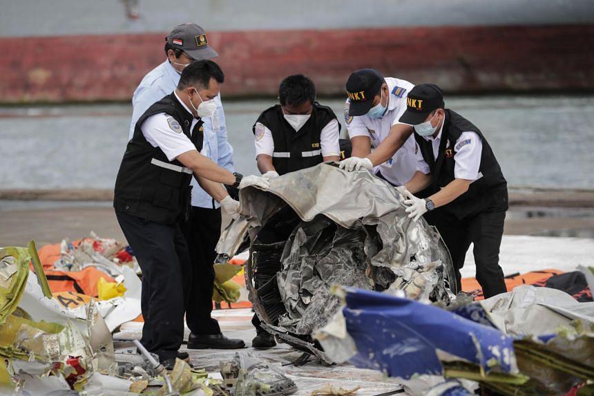 Indonesia's KNKT investigators inspect the debris of Sriwijaya Air flight SJ 182 plane recovered from the crash site on Jan 13, 2021.