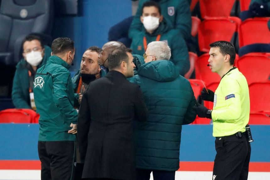 A maych day photo shows fourth official Sebastian Coltescu with Istanbul Basaksehir assistant coach Pierre Webo and referee Ovidiu Hategan with Istanbul Basaksehir coach Okan Buruk as the game is interrupted.