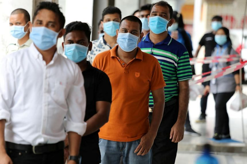 Foreign workers wait in line to be tested for Covid-19 outside a clinic in Kajang on Oct 26, 2020.