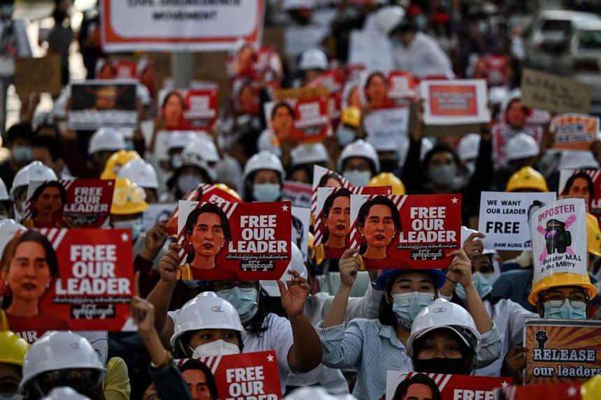 Protesters hold up placards demanding the release of detained Myanmar leader Aung San Suu Kyi during a demonstration against the coup in Yangon, on Feb 10, 2021.