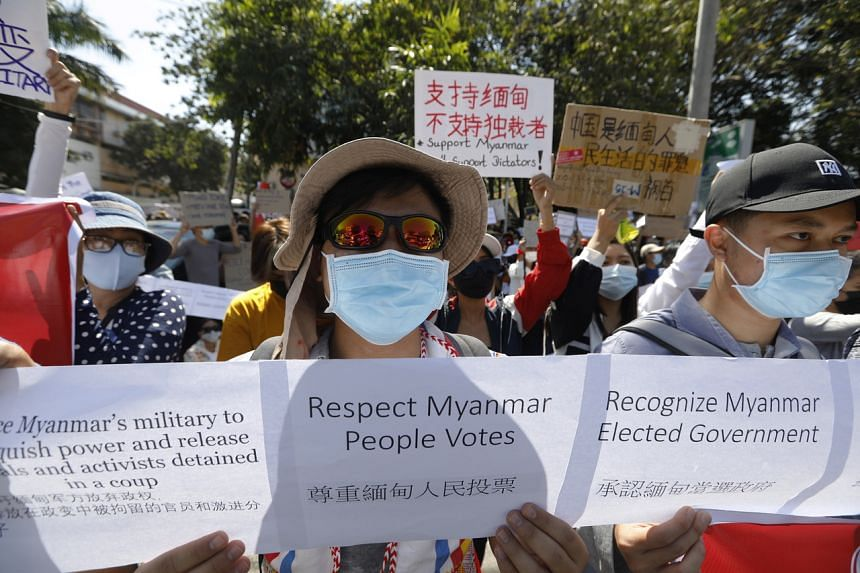 Demonstrators hold up placards during a protest in front of the Chinese Embassy in Yangon, on Feb 11, 2021.