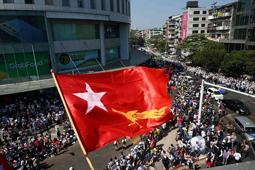The flag of the National League for Democracy party flies over coup protesters in Yangon on Feb 10, 2021.
