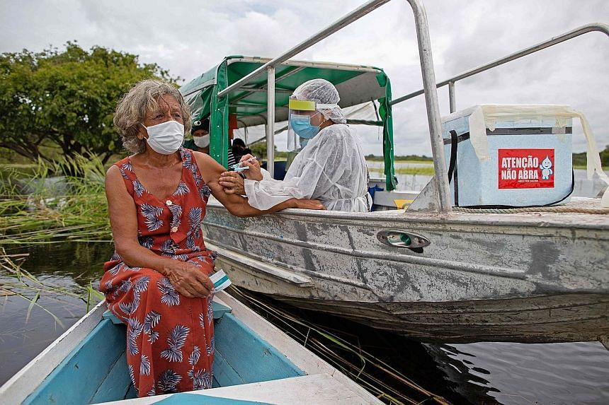 Ms Olga D'arc Pimentel, 72, getting a dose of the AstraZeneca vaccine on the banks of the Rio Negro in Amazonas state, Brazil, on Tuesday. World Health Organisation experts are awaiting more specific data on the vaccine's efficacy in people over 65,