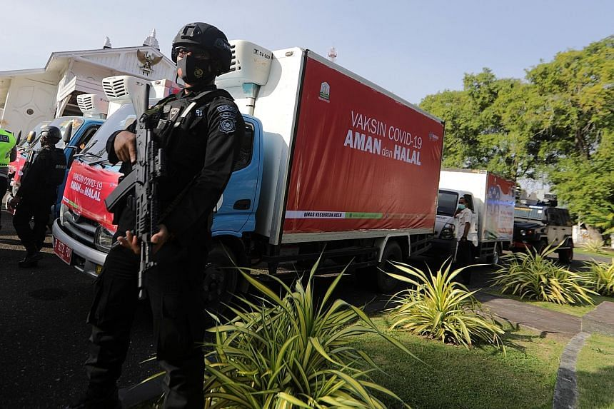 A security officer guarding containers carrying Covid-19 vaccines to be distributed to urban areas in Aceh, Indonesia, last week. Last month, state-owned pharmaceutical company Bio Farma began distributing three million doses of its Coronavac vaccine