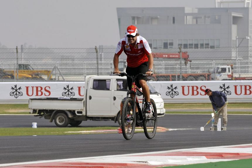 In a photo from Oct 21, 2010, Formula One driver Fernando Alonso cycles on the race track at the Korean International Circuit in Yeongam.