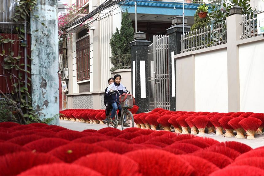 Children ride a bicycle past stacks of incense sticks drying on the street in Quang Phu Cau village, outside Hanoi, Vietnam, on Feb 3, 2021.