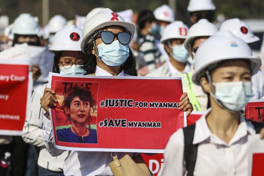 Hundreds of workers lined a road in Naypyitaw, chanting anti-junta slogans and carrying placards supporting Ms Suu Kyi.