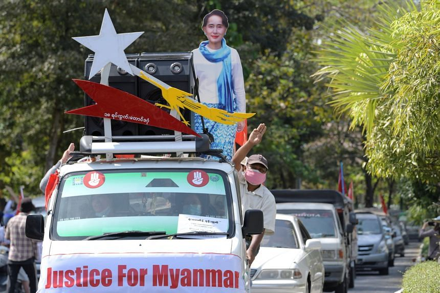 A demonstrator flashes the three-finger salute during a protest against the military coup in Yangon on Feb 12, 2021.