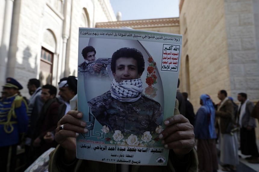 A pro-Houthi Yemeni holds a poster of his relative who was allegedly killed in recent fighting with Saudi-backed government forces.