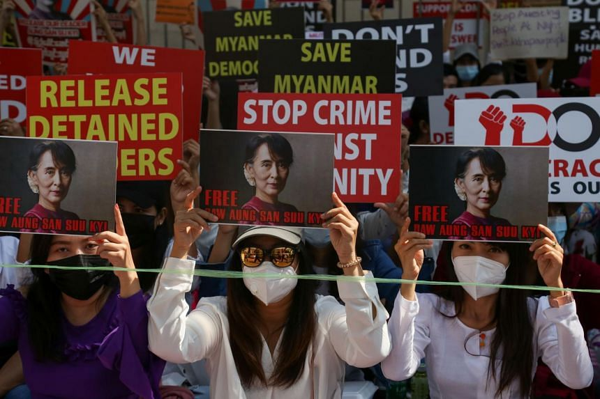Protesters hold up signs calling for the release of elected leader Aung San Suu Kyi in Yangon on Feb 13, 2021.