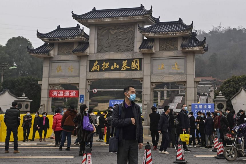 People are seen outside the Biandanshan cemetery in Wuhan on Feb 12, 2021.
