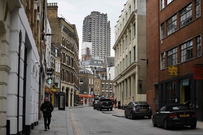 A pedestrian walks along a quiet street in London on Feb 12, 2021.