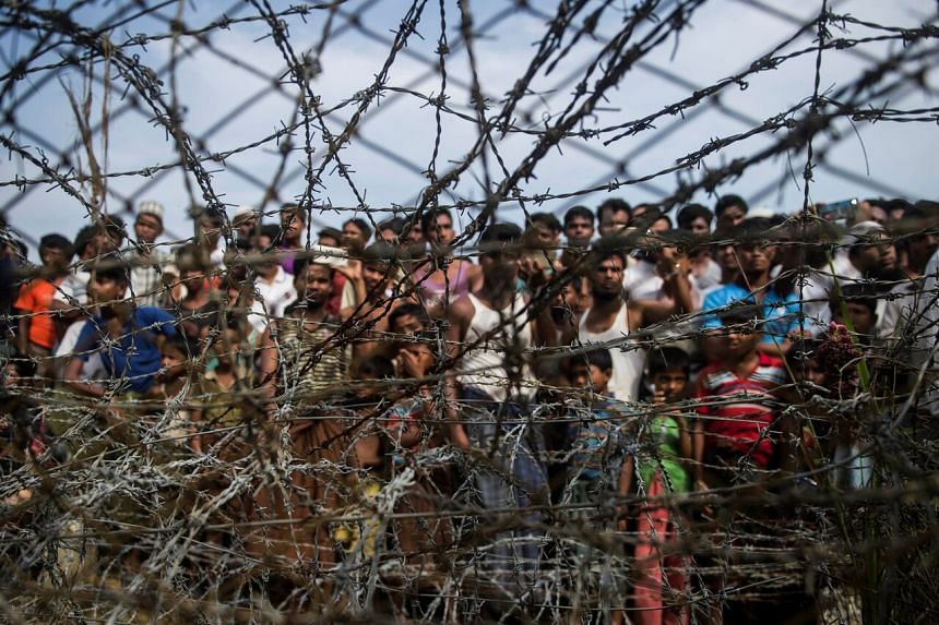 "In a photo taken on April 25, 2018, Rohingya refugees gather behind a barbed-wire fence at a temporary settlement setup in a ""no man's land"" border zone between Myanmar and Bangladesh, near Maungdaw district in Myanmar's Rakhine state."