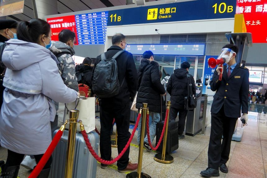 A station staff member speaks through a bullhorn to travellers waiting to board their train at Beijing South Railway station, on Feb 10, 2021.