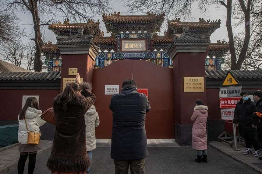 Chinese Buddhist devotees pray in front of the closed Yonghegong Lama Temple, to mark the first day of the Chinese New Year, in Beijing, on Feb 12, 2021.
