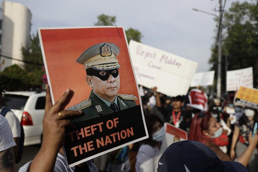 Demonstrators hold a placard with an image of Myanmar military junta chief Senior General Min Aung Hlaing during a protest outside the Chinese Embassy in Yangon on Feb 12, 2021.