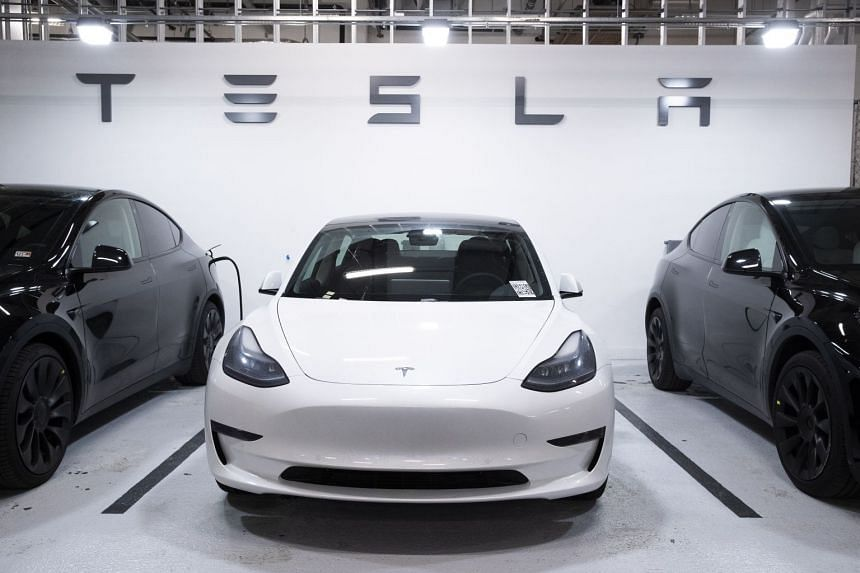 A Tesla Model 3 (centre) and two Model Ys are seen at a garage in Washington, DC.