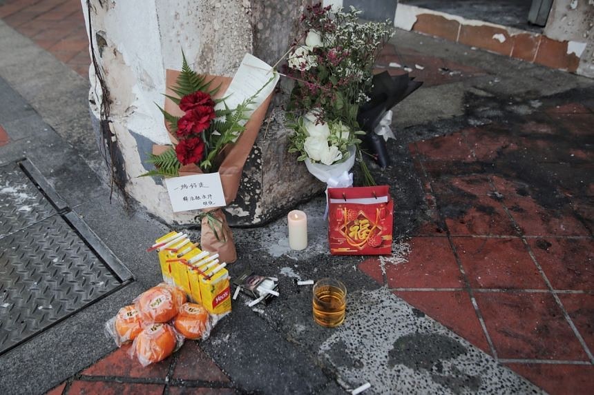 Flowers, lit candles and condolence notes were among the items placed at the side and front of the shop.