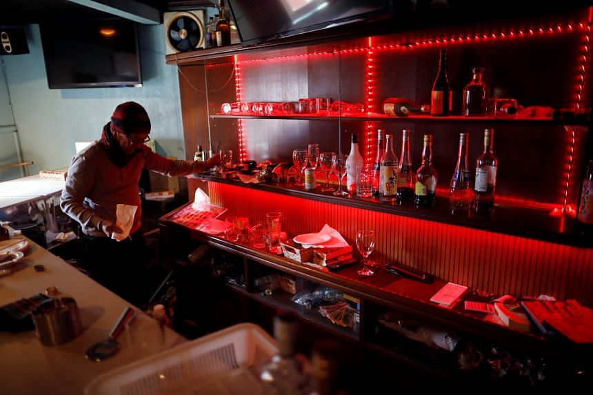 An owner of a bar cleans up broken bottles and cups at his bar after a strong quake in Iwaki, on Feb 14, 2021.