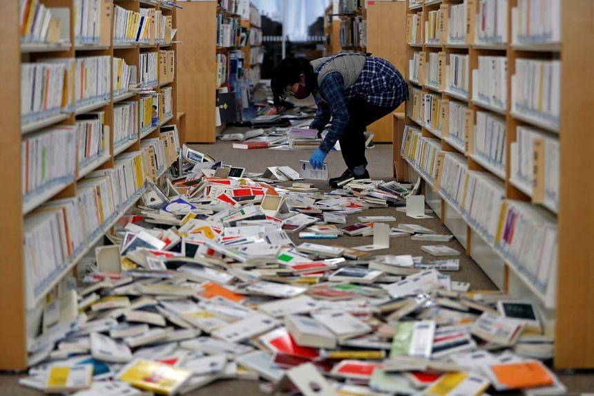 A staff member of library tries to restore books after they fell from book shelves at Iwaki City library, on Feb 14, 2021.