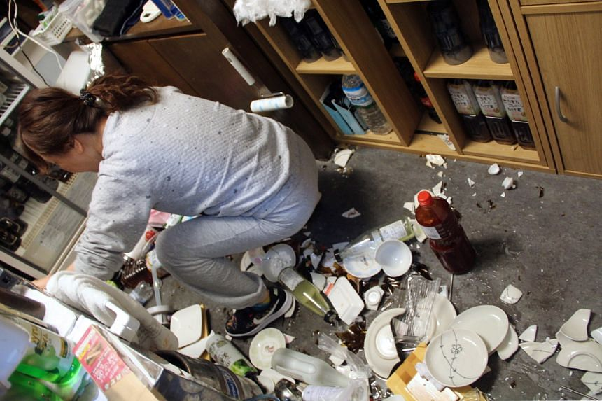 A woman cleans broken plates at a restaurant in Fukushima, on Feb 14, 2021.