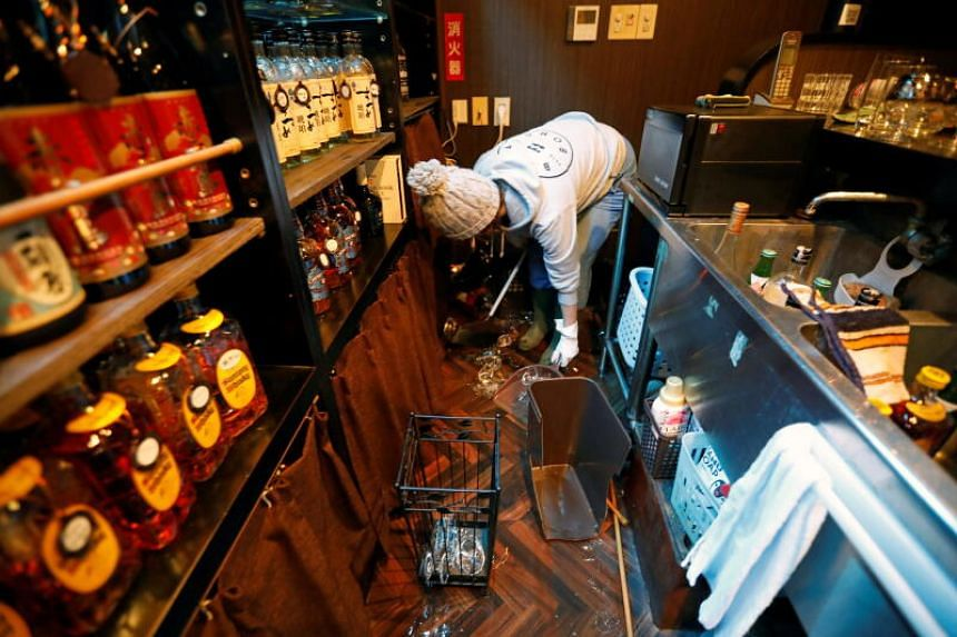 A bar-owner clearing broken bottles at a her shop after a strong earthquake hit the region, in Iwaki,  in Japan's Fukushima prefecture, on Feb 14, 2021.