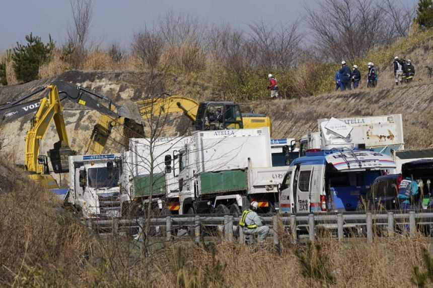 Construction teams removing mud following a landslide covering the Joban Expressway in Soma, Fukushima prefecture, in the aftermath of a strong earthquake, on Feb 14, 2021.