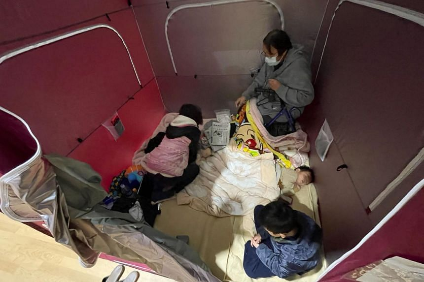 A family resting inside a shelter set up in a sports arena in Soma, Fukushima, on Feb 14, 2021.
