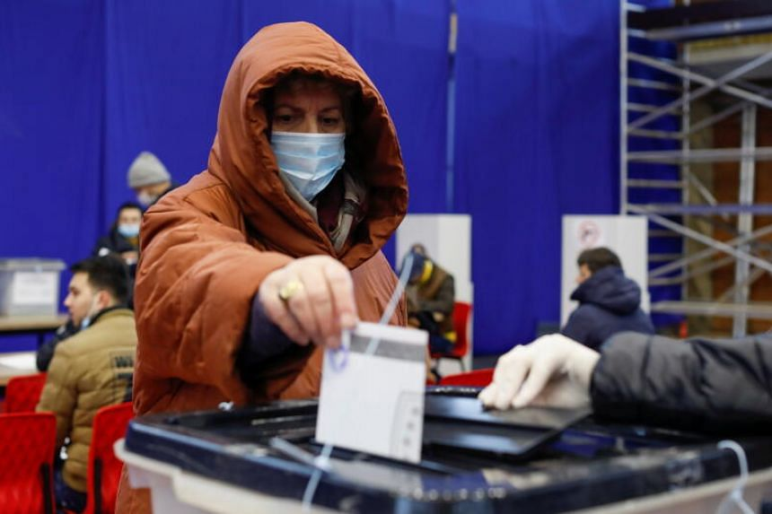 A voter casting her ballot during parliamentary elections in Pristina, Kosovo, on Feb 14, 2021.