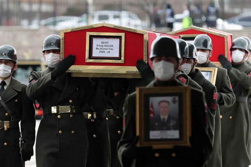 Turkish military personnel carrying the coffins of three soldiers who were killed during a clash with Kurdish militants in Iraq, during the funeral service in Ankara, Turkey, on Feb 12, 2021.