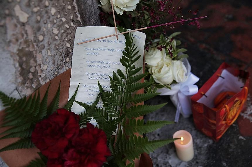 A woman (left), who said she was a family member, at the scene of the accident around mid-morning yesterday. She placed a bouquet of blue flowers at the scene, and removed a photograph and clothing that had been placed there. A condolence note that w