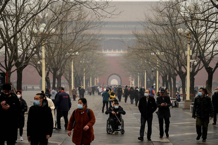 People arrive at the entrance to the Forbidden City in Beijing on Feb 13, 2021.